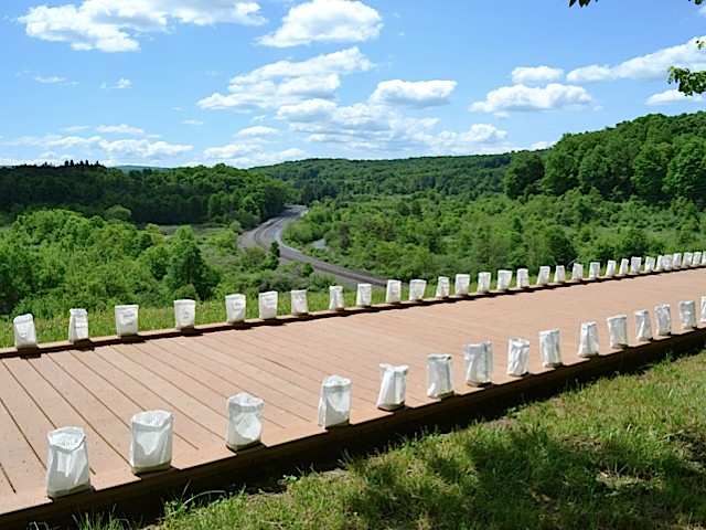 Luminary bags, each one bearing the name of a flood victim, line a walkway on top of what remains of the South Fork Dam.